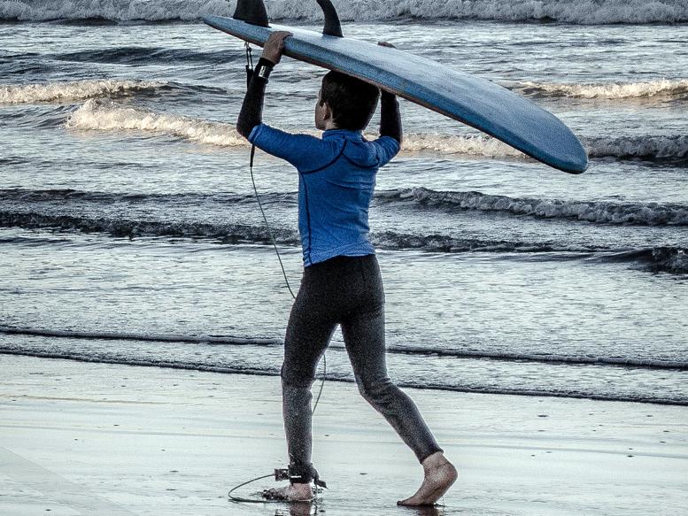 surfer trägt surfboard am strand